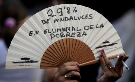 TERCERA SEMANA: Una mujer protesta con un abanico donde dice '29, 8% De los andaluces en el umbral de la pobreza', contra las medidas del gobierno español de austeridad más recientes, en Sevilla, el 19 de julio de 2012.