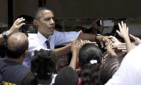 El presidente Barack Obama saluda a personas afuera del restaurante Lechonera El Barrio, en Orlando, Florida, el jueves 2 de agosto de 2012. Obama tenía previsto para el jueves actos de campaña en Florida y el Norte de Virginia. El equipo de campaña del mandatario busca cortejar a los electores puertorriqueños en Florida.