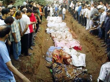 Sirios entierran a sus muertos en Damasco, en una foto difundida por la Red de Noticias Shaam el 1 de agosto del 2012, Activistas sirios de oposición dicen que las fuerzas del règimen allanaron vecindarios del sur de la capital Damasco en una mortìfera operaciòn militar que ha provocada bajas.