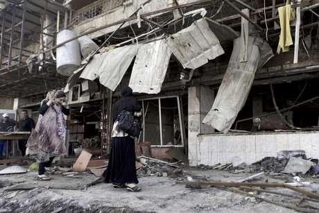 Iraquíes inspeccionan los daños causados por la explosión de un coche bomba en un área mercantil de Karradah, Bagdad, Irak, el miércoles 1 de agosto del 2012. Dos ataques desde vehículos en marcha en un suburbio del oeste de Bagdad causaron la muerte a tres soldados iraquíes y un policía, informaron las autoridades el viernes 3 de agosto del 2012.