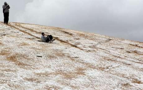 Un joven se desliza por una colina tras una inusual nevada en Johannesburgo, el martes 7 de agosto del 2012.