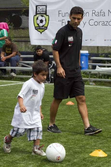 Rafa watches as a kid dribbles the ball past him as he helps in the training in New York.