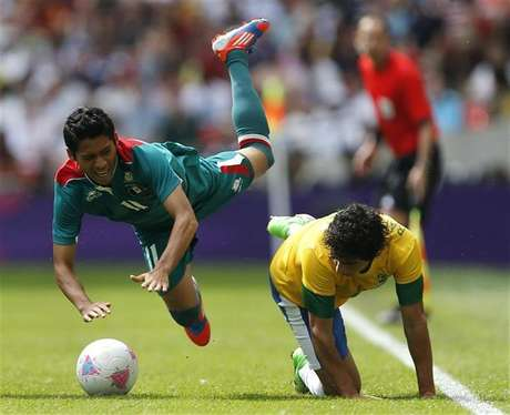 Mexico's Javier Aquino (L) falls over Brazil's Rafael during their men's football gold medal match at Wembley Stadium during the London 2012 Olympic Games August 11, 2012.