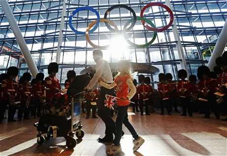 Travellers pass the Olympic Rings during an unveiling ceremony in the Terminal Five arrivals hall at Heathrow Airport, in preparation for the London 2012 Olympic Games in London June 20, 2012.