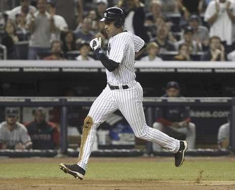 Derek Jeter, de los Yanquis de Nueva York, anota una carrera por un lanzamiento descontrolado de Josh Beckett, de los Medias Rojas de Boston, en el partido del domingo 19 de agosto de 2012 en el Yankee Stadium.