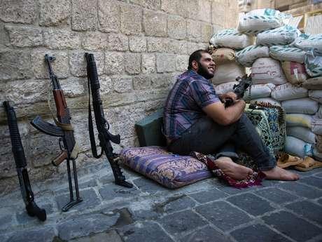 Un miembro del Ejército Sirio de Liberación, el principal grupo armado rebelde, controla una barricada en una calle de la antigua ciudad de Alepo, declarada Patrimonio Histórico de la Humanidad por la UNESCO y que está quedando gravemente afectada por los combates y bombardeos.