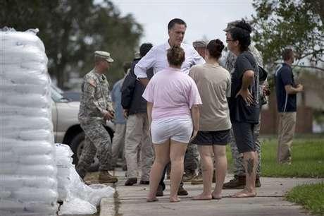 Mitt Romney habla con personas que sufrieron inundaciones por el huracán Isaac.