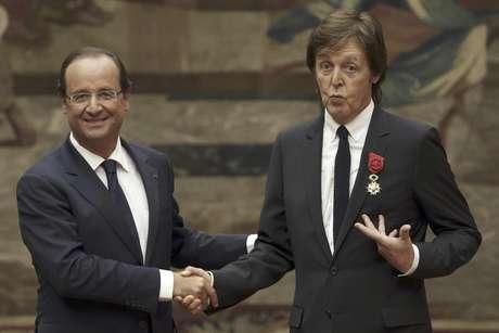 El presidente francés Francois Hollande, izquierda, estrecha la mano del ex Beatle Paul McCartney tras condecorarlo con la Legión de Honor en el Palacio del Eliseo en París, el sábado 8 de septiembre de 2012.