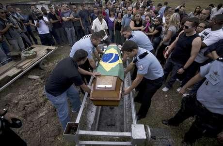 Varios policías colocan en la tumba el féretro con los restos de su compañero caído Diego Bruno Barbosa Henriques, en un cementerio en Río de Janeiro, Brasil, el viernes 14 de septiembre de 2012. Una bandera brasileña cubre el ataúd. Barbosa fue asesinado con arma de fuego el jueves en la noche mientras efectuaba un patrullaje a pie en el barrio pobre de Rocinha, en la ciudad. Barbosa es el tercer agente asesinado en los barrios pobres en los que las autoridades han reinstalado el orden en Río.