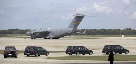 Cuatro coches fúnebres con los restos de los estadounidenses muertos esta semana en Bengasi, Libia, junto al avión en que llegaron, van rumbo a la ceremonia fúnebre el 14 de septiembre del 2012 en la Base Andrews de la Fuerza Aérea en Maryland