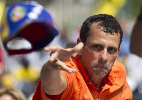 Opposition candidate Henrique Capriles throws his cap to supporters during an election rally in Caracas September 16, 2012.