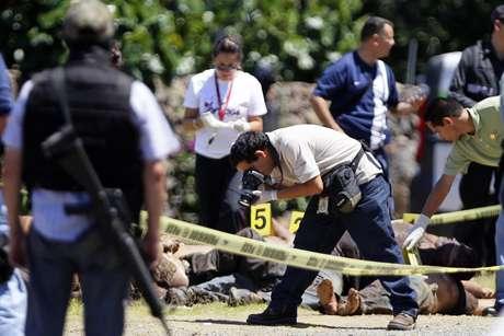 Trabajadores forenses realizan el levantamiento de 17 cadáveres el domingo 16 de septiembre de 2012, en la carretera que une los estados de Michoacán y Guadalajara.