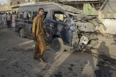 A resident walks past a damaged vehicle at the site of a bomb attack on the outskirts of Peshawar September 19, 2012. A bomb in Peshawar killed at least 10 people and wounded more than 30 on Wednesday, police said. The bomb seemed to be targeting a van carrying officials from the Pakistan Air Force, said a local police official.