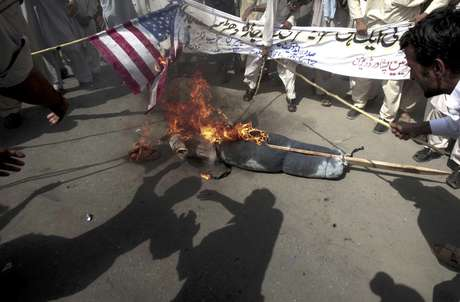Manifestantes paquistaníes queman una bandera de Estados Unidos y una imagen del presidente estadounidense Barack Obama durante un mitin en Peshawar, Pakistán, como parte de la ira generalizada en el mundo musulman por una película hecha en territorio estadounidense que critica al profeta Mahoma, el jueves 20 de septiembre de 2012.