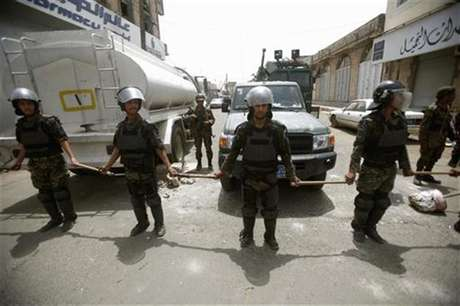 Riot policemen stand guard outside the French embassy in Sanaa September 20, 2012.