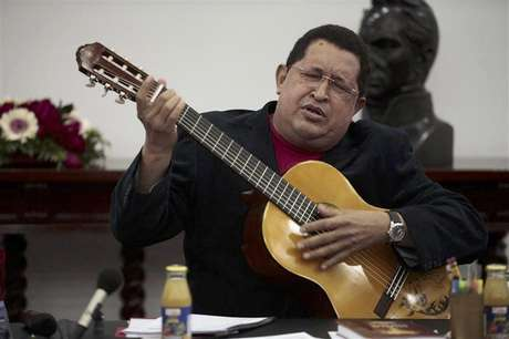 Venezuelan President Hugo Chavez plays a guitar, which was a gift from Mexican singer Vicente Fernandez, during a cabinet meeting at Miraflores Palace in Caracas September 20, 2012.