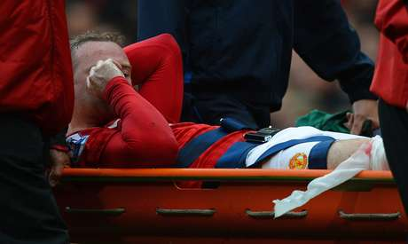 Manchester United's English striker Wayne Rooney leaves the pitch on a stretcher after injuring his knee during the English Premier League football match between Manchester United and Fulham at Old Trafford in Manchester, north-west England on August 25, 2012.