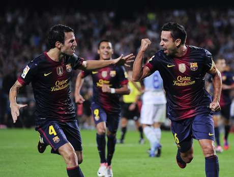 Cesc Fabregas and Xavi Hernandez celebrate the latter's goal in a 2-0 win over Granada