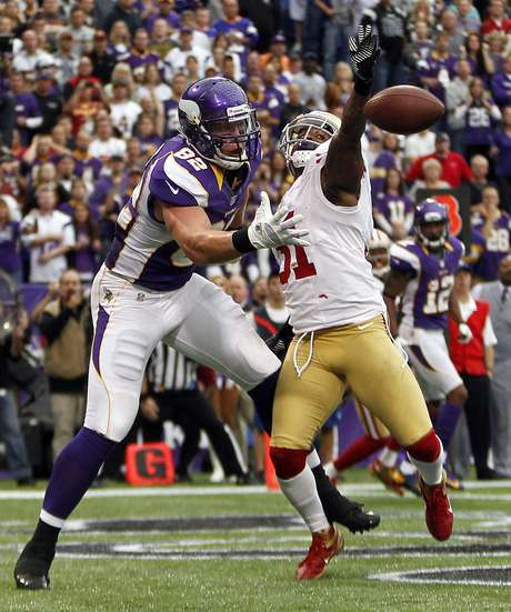 Minnesota Vikings tight end Kyle Rudolph (82) catches a touchdown pass around San Franciso 49ers safety Donte Whitner (R) during the second half of their NFL football game in Minneapolis, September 23, 2012.