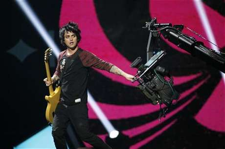 Green Day lead vocalist and guitarist Billie Joe Armstrong grabs a camera during the 2012 iHeart Radio Music Festival at the MGM Grand Garden Arena in Las Vegas, Nevada September 21, 2012.