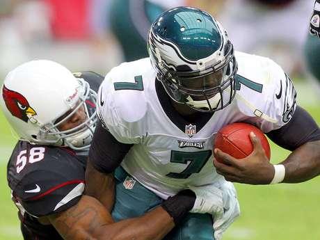 El linebacker Daryl Washington detiene al quarterback Michael Vick.