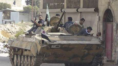 Members of the Free Syrian Army are seen around a captured Syrian Army tank after clashes, at Marat al-Numan, near the northern province of Idlib October 9, 2012. Picture taken October 9, 2012.