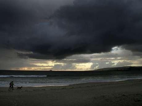 Una pareja pasea su perro en la playa el lunes 15 de octubre de 2012, en Ensenada, estado mexicano de Baja California, donde se esperan lluvias debido a la aproximación de 'Paul'.