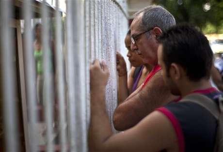 Cubanos averiguan sobre la nueva disposición para salir del país en una oficina de migración de La Habana.