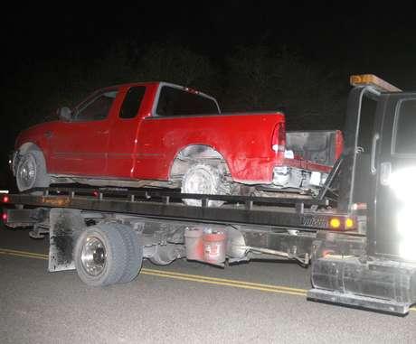 Una camioneta pick up es retirada del lugar donde fue baleada desde un helicóptero por un policía estatal durante una persecución cerca de La Joya, Texas, el jueves 25 de octubre de 2012.