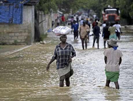 Unas personas caminan por calles inundadas por el huracán Sandy, en La Plaine, Haití, el jueves 25 de octubre de 2012. El huracán dejó al menos 69 muertos en su paso por el Caribe y se dirige a costa este de EEUU.