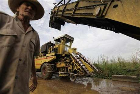 A farmer walks beside two combined harvesters being serviced after cutting sugar cane in the fields near the village of Viana, province of Villa Clara in central Cuba in this file photo taken February 24, 2010.
