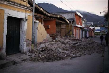 Two men walk past damaged houses after a 7.4-magnitude earthquake struck on Wednesday on the streets of San Marcos, in the San Marcos region, about 250 km (155 miles) south of Guatemala City, November 8, 2012.