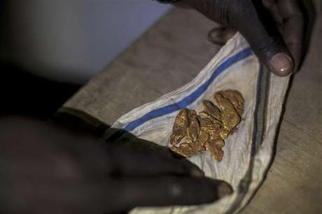 A man shows off his gold to potential buyers in a hotel in Kapoeta, South Sudan September 27, 2012.