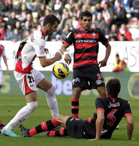 El delantero brasileño del Rayo Vallecano Leo Baptistao (i) intenta marcharse del defensa Jonathan Vila (suelo) y el centrocampista argentino Augusto Fernández (c), ambos del Celta, durante el partido correspondiente a la undécima jornada de la Liga de Primera División disputado en el estadio municipal de Vallecas.