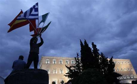 A protestor raises flags of Portugal, Italy, Greece and Spain in front of the parliament in Syntagma square during a 48-hour strike by the two major Greek workers unions in central Athens November 7, 2012.