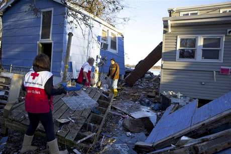 Red Cross volunteers Jessica Elam and Gilbert Abney check on Rob Fragetti, who is attempting to salvage items with his neighbors in their destroyed homes, in this handout photo from the American Red Cross, in Staten Island, New York, in this November 6, 2012 file photo.