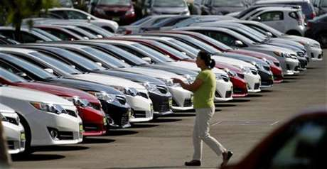 A woman walks by vehicles for sale at a Toyota dealership in Pasadena, California October 10, 2012.