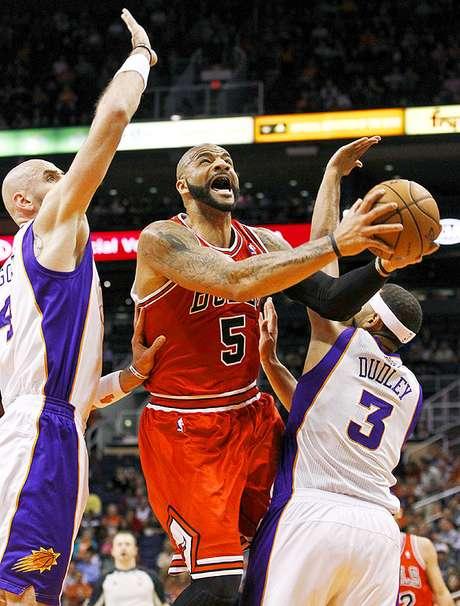 Bulls vs. Suns: Carlos Boozer (5) intenta un disparo ante la marca de Marcin Gortat y Jared Dudley (3). Chicago tuvo que emplearse en tiempo extra para vencer 112-106 a Phoenix en el US Airways Center.