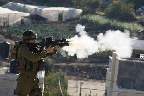 Un soldado israelí dispara gases lacrimógenos contra manifestantes palestinos en una ciudad de la Franja de Gaza.
