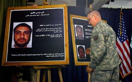 A U.S. solider shows a picture of Ali Mussa Daqduq (L) during a news conference at the heavily fortified Green Zone area in Baghdad July 2, 2007.