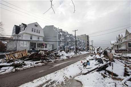 Snow left by a nor'easter, also known as a northeaster storm, covers piles of debris piled up outside of peoples homes due to the flooding from hurricane Sandy in the Queens borough neighborhood of Rockaway Beach, New York, November 8, 2012.
