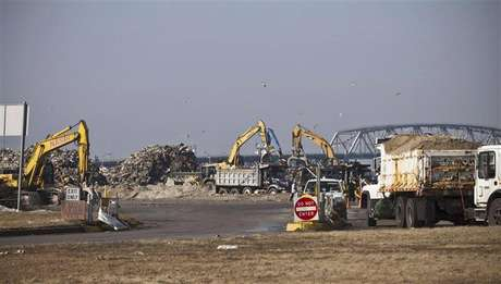 Garbage trucks wait to enter the parking lot at Jacob Riis Park, which has been converted temporarily into a landfill to accommodate all the debris and garbage created by Hurricane Sandy, in the Neponsit neighborhood of Queens, New York in this November 11, 2012 file photo.The temporary garbage dump at Jacob Riis Park in Queens is one of several sites around the city.