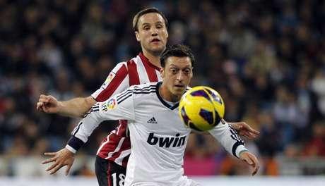 El jugador del Athletic de Bilbao Carlos Gurpegi defiende al madridista Mesut Özil
