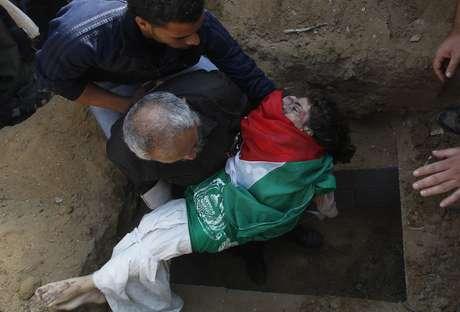 El cuerpo de uno de los tres niños de una familia palestina muertos en el bombardeo israelí del domingo es enterrado en Gaza.