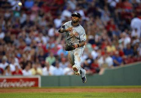 Miami Marlins shortstop Jose Reyes throws out Boston Red Sox Dustin Pedroia at first base in the third inning of their MLB interleague baseball game at Fenway Park in Boston, Massachusetts June 21, 2012.