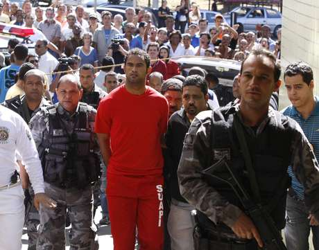 Brazilian footballer Bruno Fernandes de Souza (in red) is taken under custody to the presidium of Belo Horizonte, Brazil, on July 9, 2010. De Sousa, a star goalkeeper for the popular Brazilian club Flamengo, surrendered to police Wednesday to face questioning in connection with the disappearance of his ex-girlfriend, officials said.