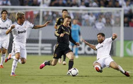 Los Angeles Galaxy's David Beckham (C) chases the ball between Real Madrid's Fabio Coentrao (L) and Xabi Alonso (R) during the first half of their World Football Challenge international friendly soccer match in Carson, California August 2, 2012.