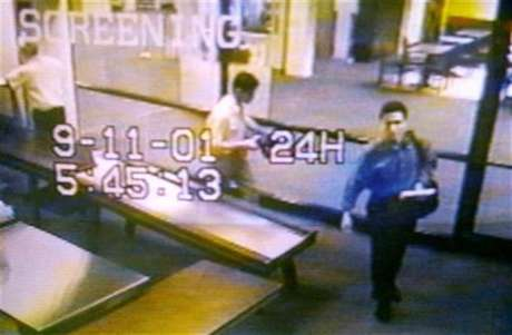 Two men identified by authorities as suspected hijackers Mohammed Atta (R) and Abdulaziz Alomari (C) pass through airport security September 11, 2001 at Portland International Jetport in Maine in an image from airport surveillance tape released September 19, 2001.