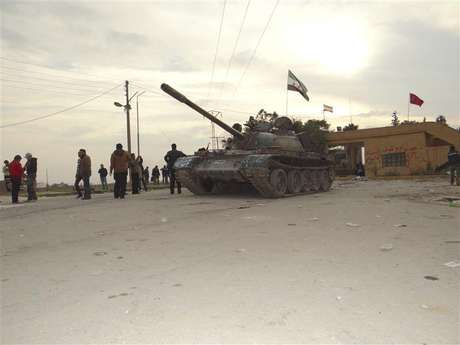 Residents and Free Syrian Army fighters pose near a tank after the fighters said they fought and defeated government troops from the town of Ras al-Ain, near the province of Hasaka, 600 km (375 miles) from Damascus, November 22, 2012.