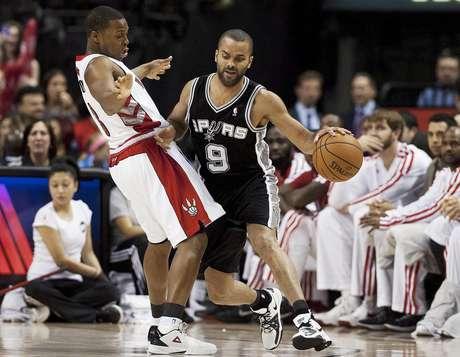 El francés Tony Parker (9) de los Spurs de San Antonio trabaja contra la marca de Kyle Lowry, izquierda, de los Raptors de Toronto durante la primera mitad del encuentro del domingo 25 de noviembre de 2012, en Toronto.